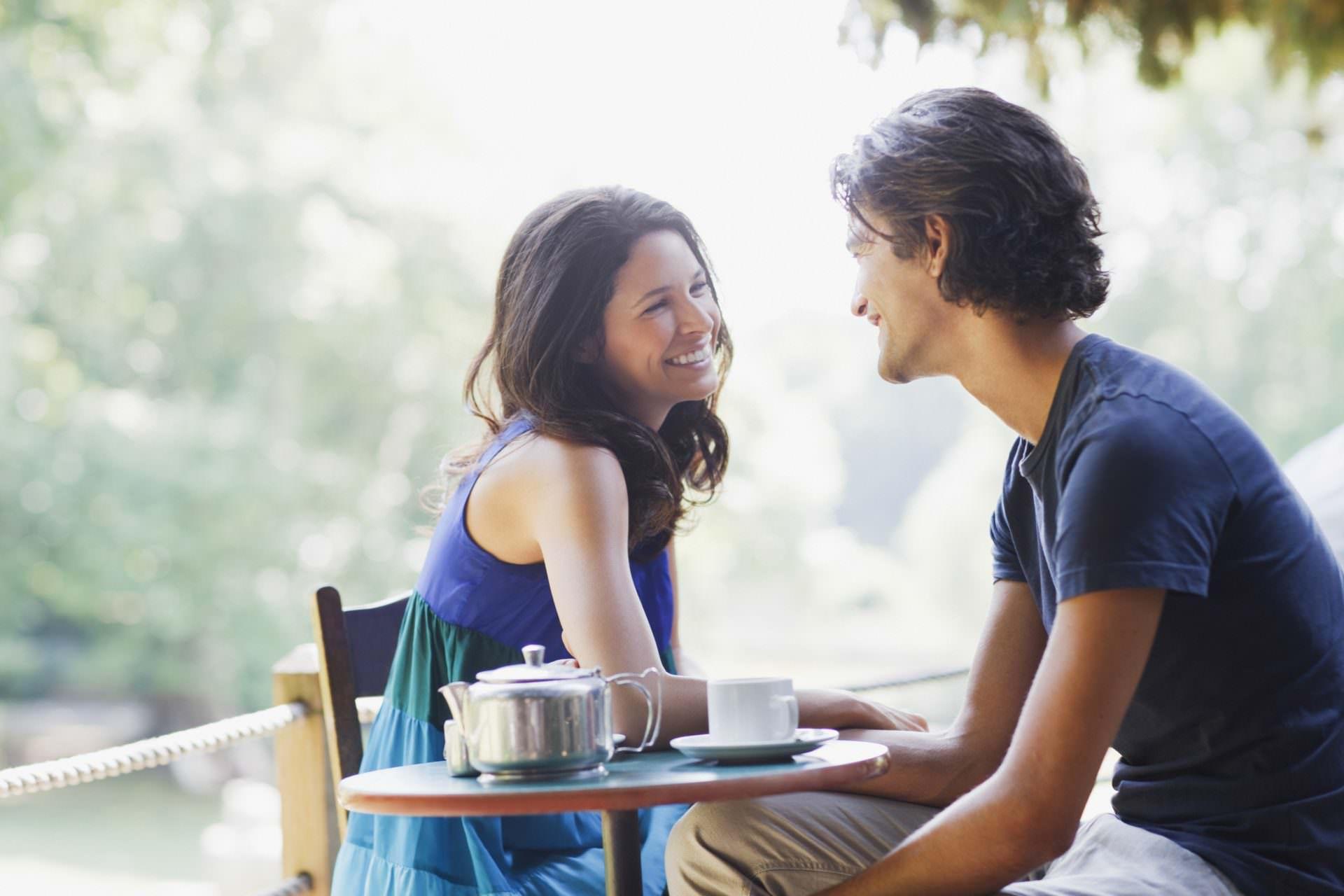 Smiling couple having tea outdoors