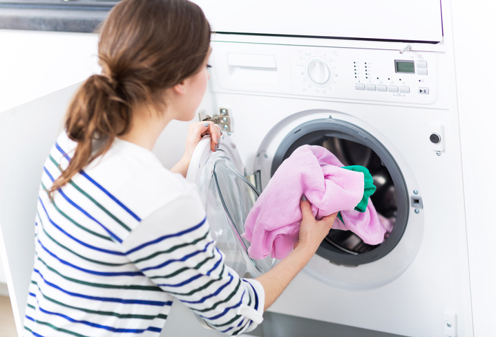 Woman Putting her Laundry into a Washing Machine