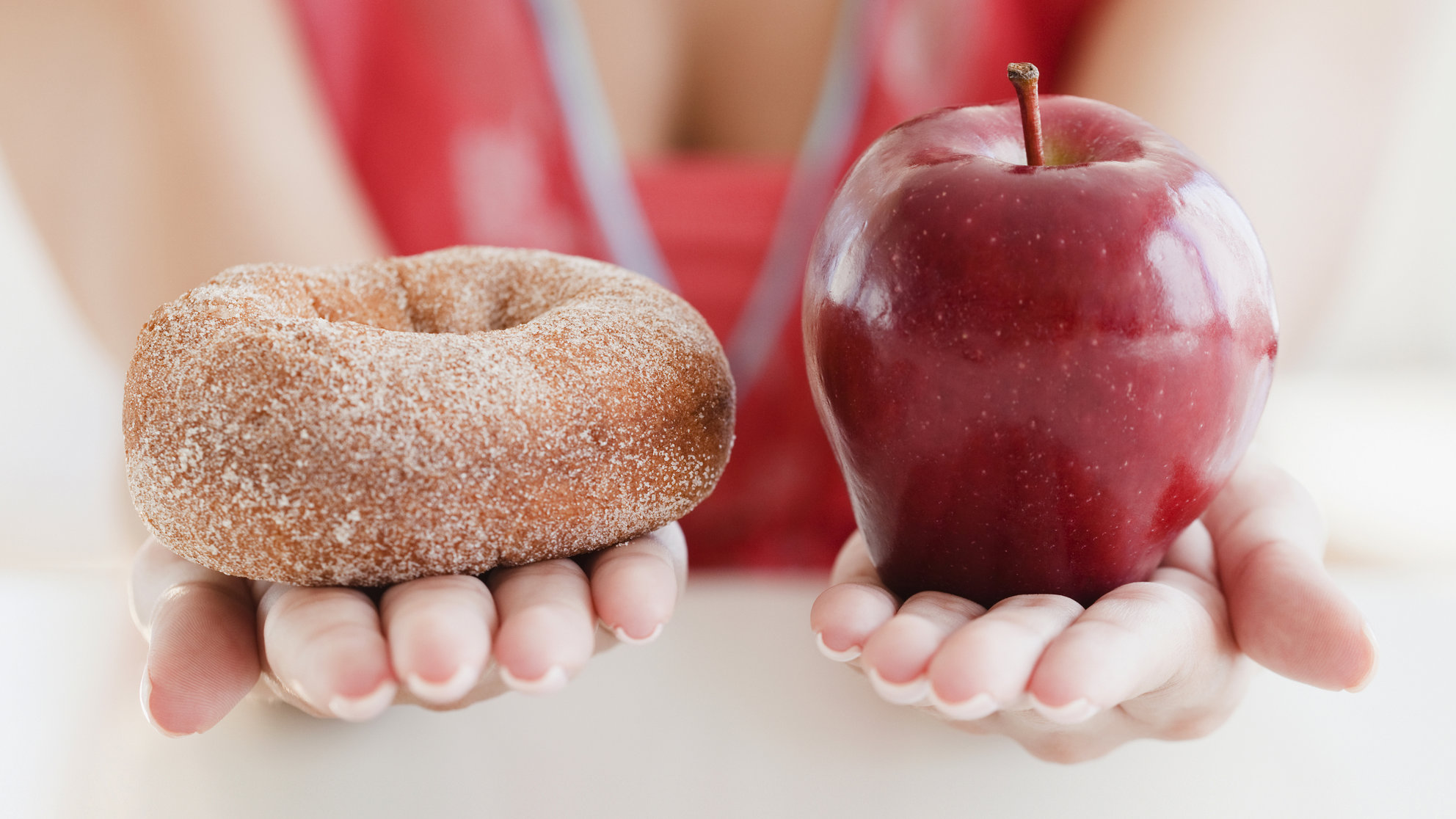 USA, New Jersey, Jersey City, Close up of woman's hands holding donut and apple