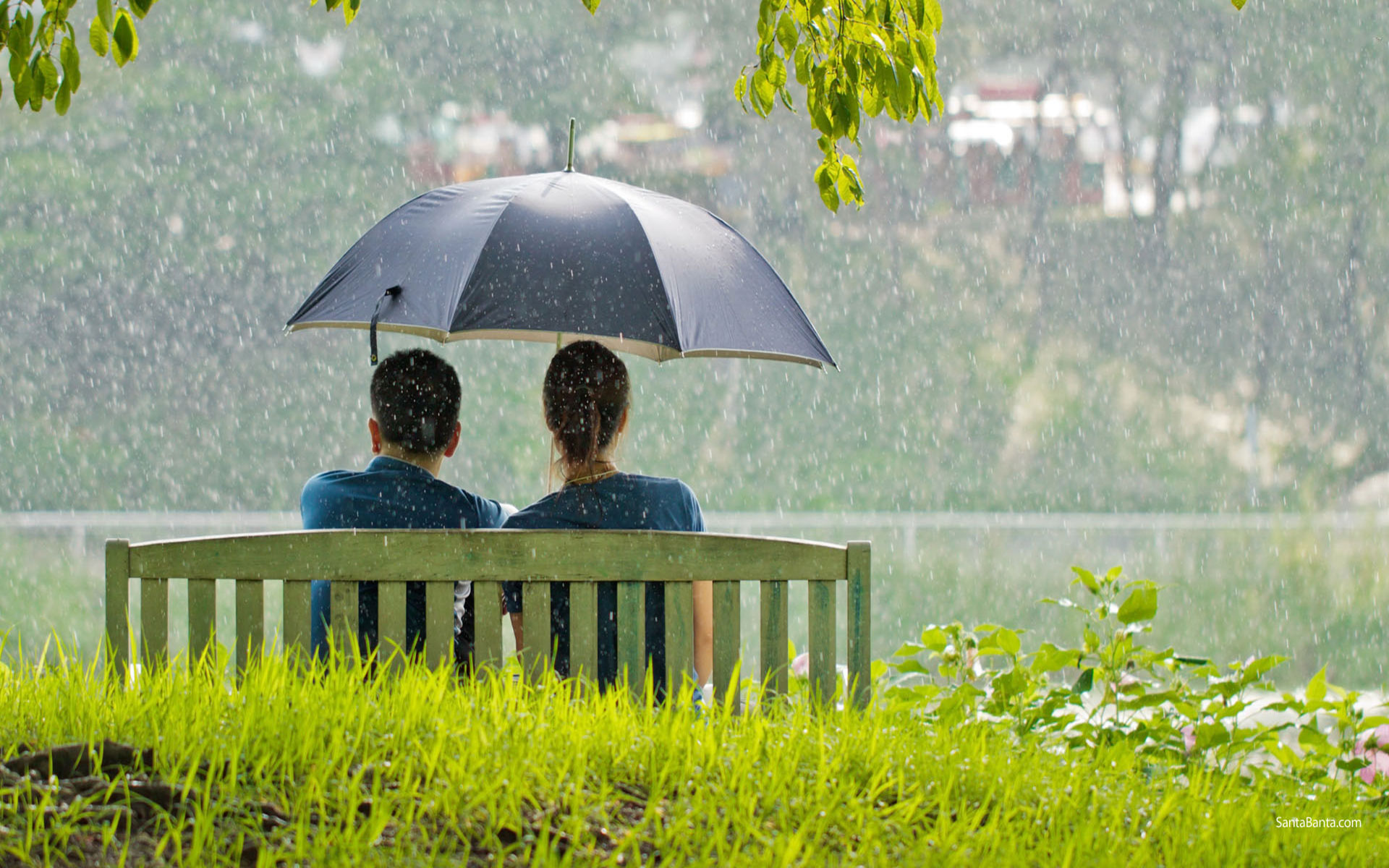 Romantic-couple-sitting-in-park-while-raining