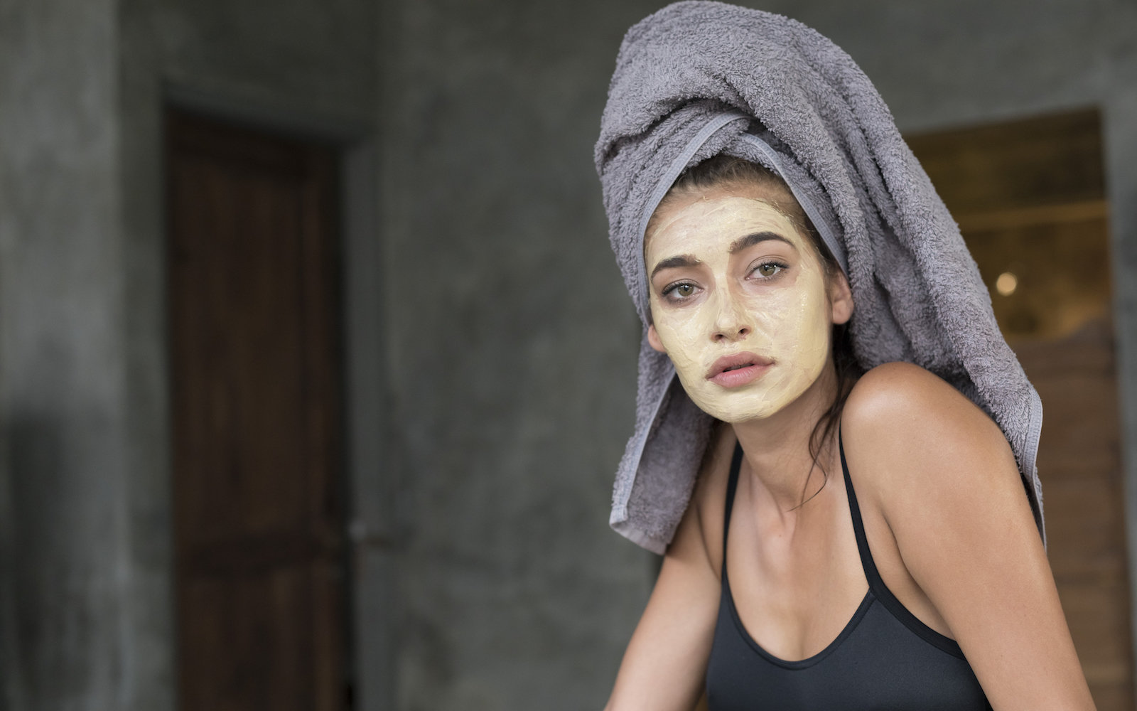 Woman with a face mask and a towel on her head