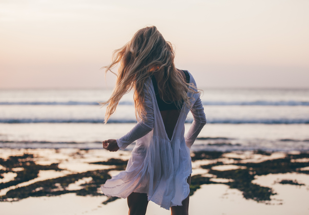 Beautiful blonde girl with long hair in short white dress dancing at sunset