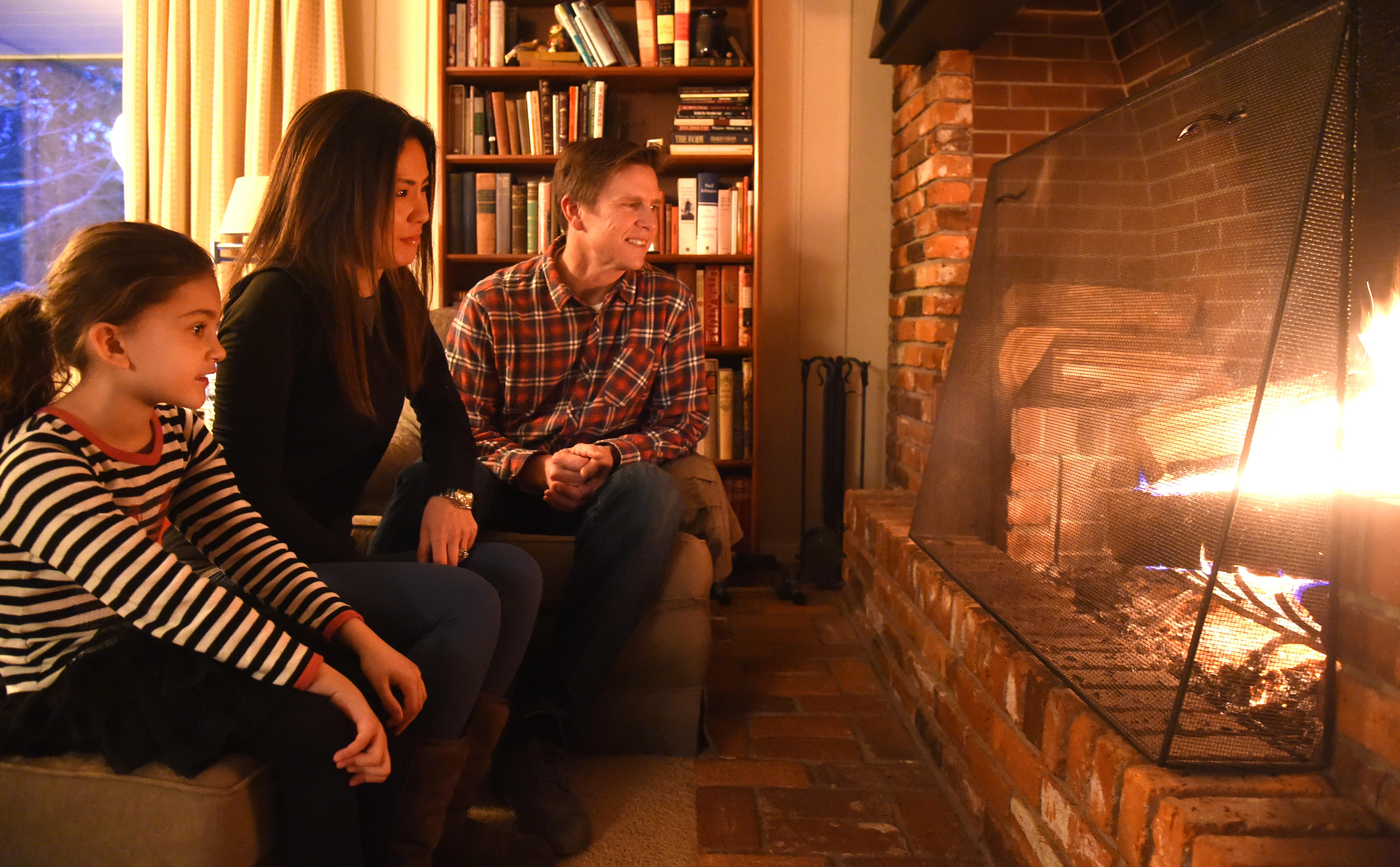 Patrick and Ting Vollmer with daughter Zoe, 6, sit in front of their fire place Friday, Nov. 27, 2015, after being one of the last customers to get power restored by the utility company. They stayed with family, eventually found a generator and survived the last few days. JESSE TINSLEY jesset@spokesman.com
