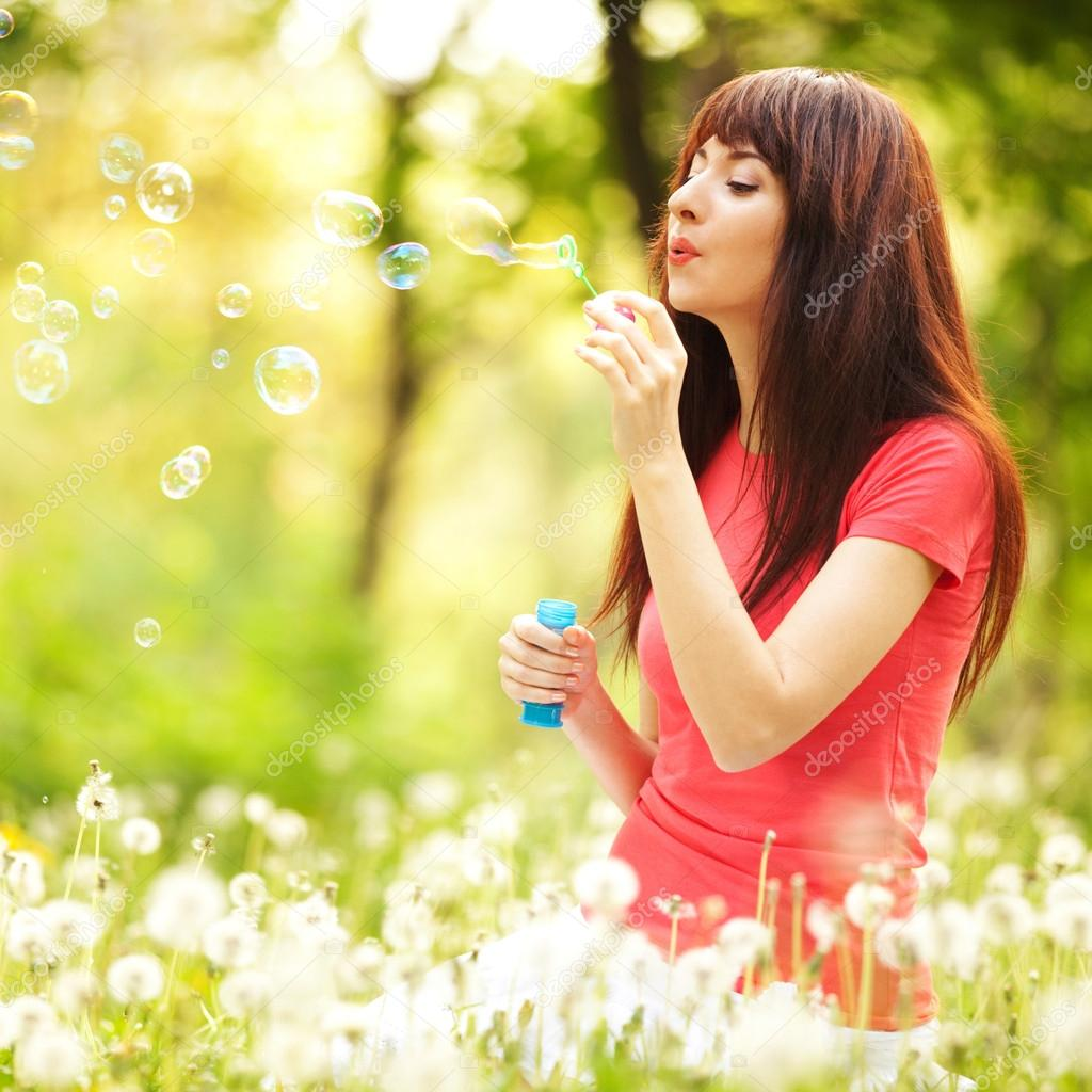 depositphotos_18047913-stock-photo-happy-woman-blowing-bubbles-in