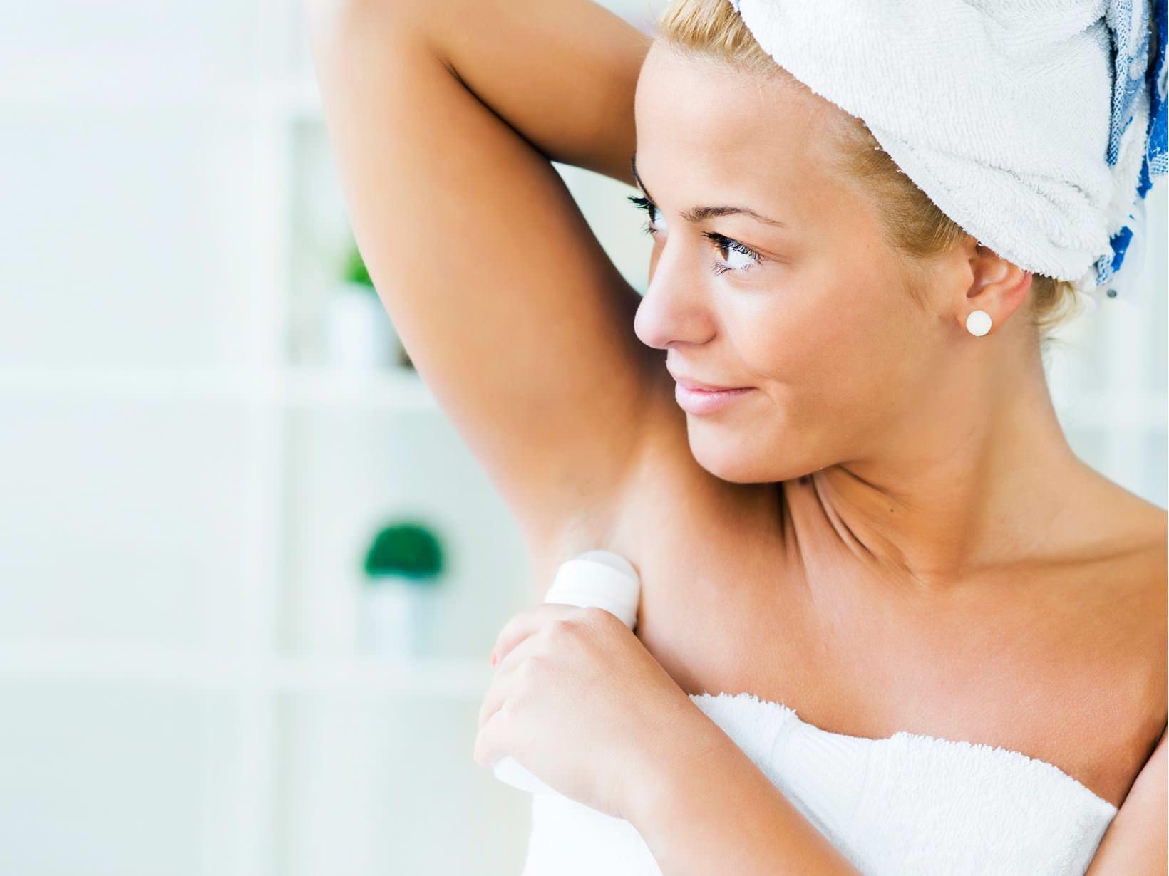 woman-applying-deodorant-in-bathroom