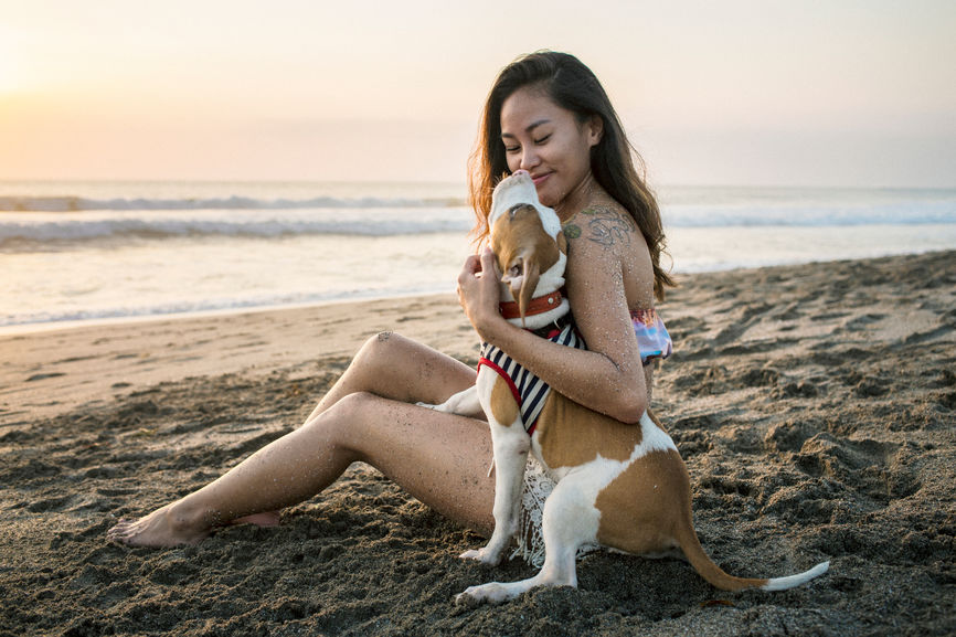 Young Asian Woman With Her Dog At Beach