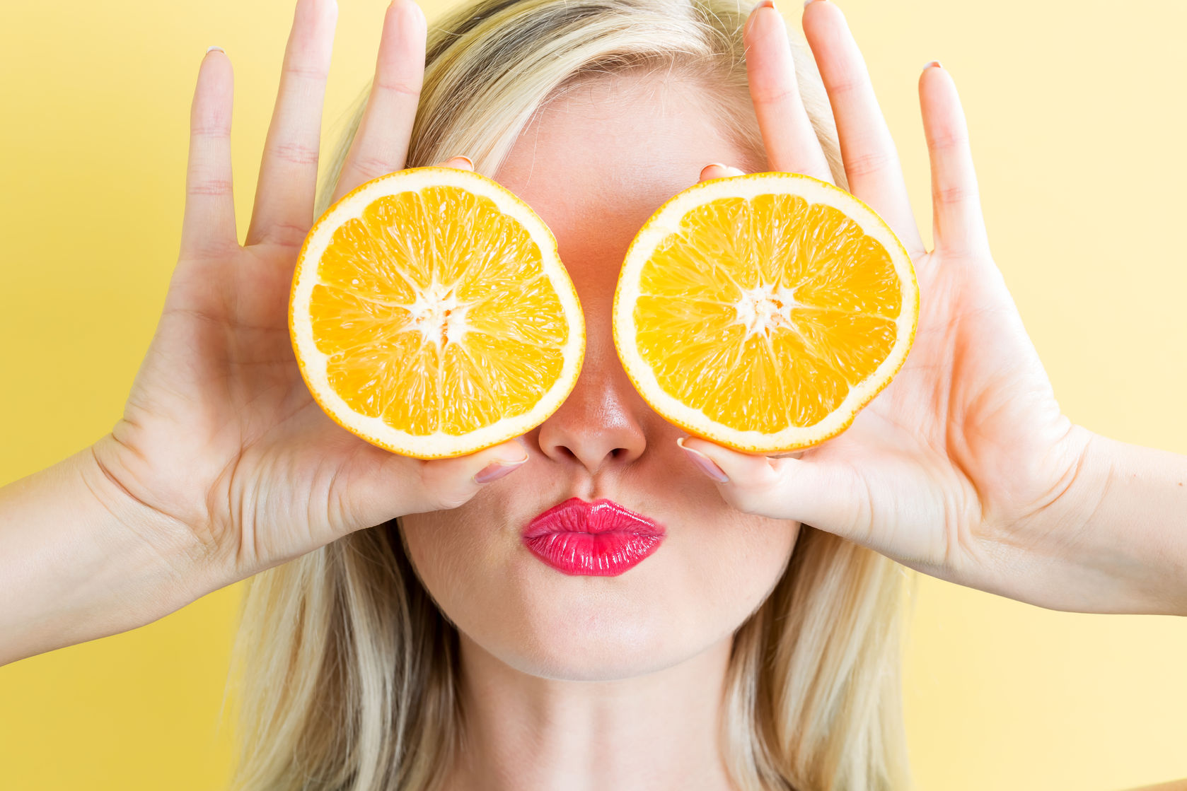 63993742 - happy young woman holding oranges on a yellow background